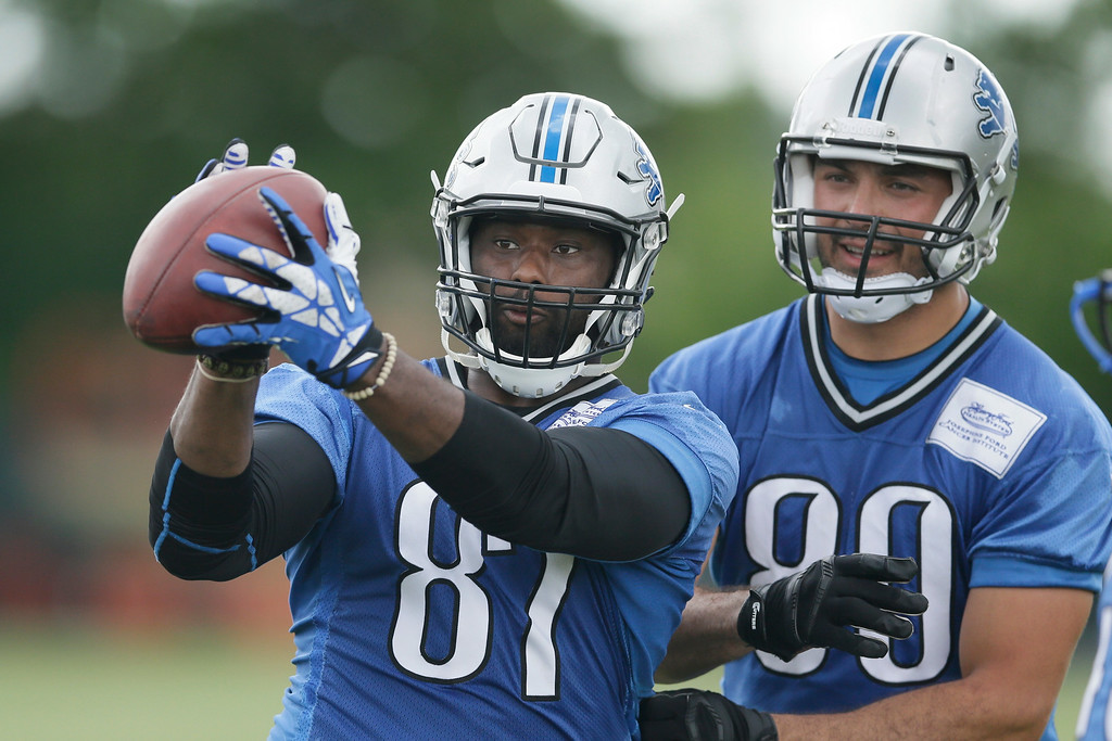 . Detroit Lions tight end Brandon Pettigrew catches a ball through the distraction of teammates during an NFL football minicamp in Allen Park, Mich., Wednesday, June 11, 2014. (AP Photo/Carlos Osorio)