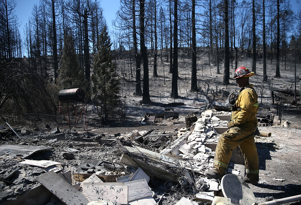 . A firefighter surveys the remains of a destroyed home on September 16, 2014 in Weed, California. A fast moving wildfire fueled by high winds ripped through the town of Weed on the afternoon of September 15, burning 100 structures including the high school and lumber mill.  (Photo by Justin Sullivan/Getty Images)