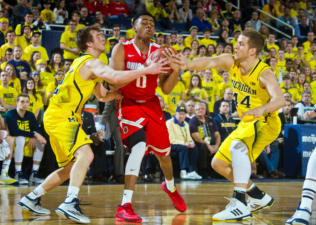 . Ohio State guard D\'Angelo Russell (0) tries to keep the ball while challenged by Michigan guard Spike Albrecht, left, and forward Max Bielfeldt, right, in the first half of an NCAA college basketball game at Crisler Center in Ann Arbor, Mich., Sunday, Feb. 22, 2015. (AP Photo/Tony Ding)