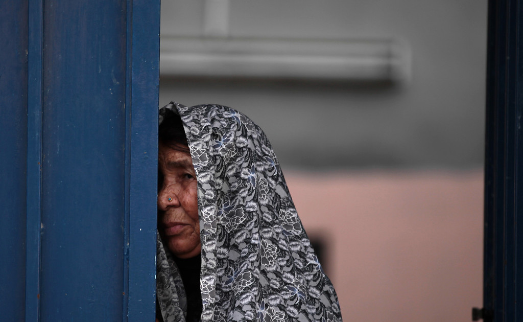 . An elderly Bahraini woman looks out from a doorway during a funeral procession of Ali Jaffar Habib, 10, in Malkiya village, Bahrain, Saturday, Aug. 10, 2013. The boy\'s family and opposition activists blamed cancer, the cause of the boy\'s death, was due to repeated heavy tear gas exposure. (AP Photo/Hasan Jamali)