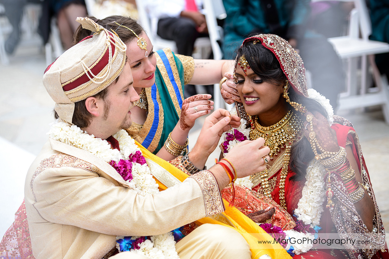 groom placing mangalsutra on bride's neck, indian wedding ceremony at Brazilian Room - Tilden Regional Park, Berkeley