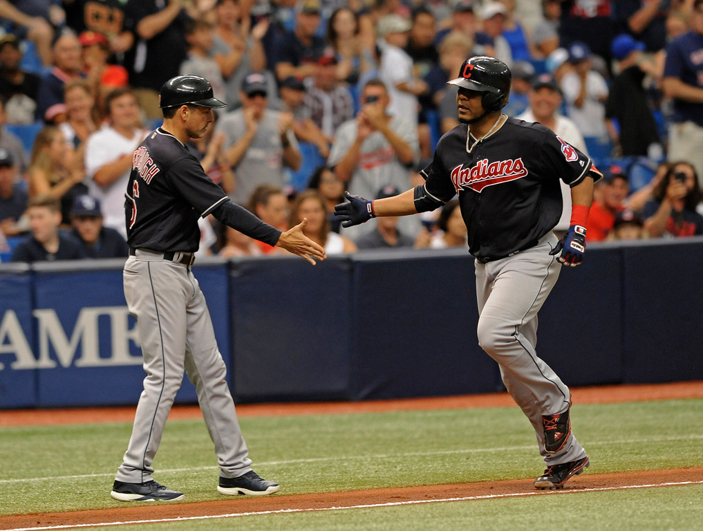 . Cleveland Indians third base coach Mike Sarbaugh congratulates Edwin Encarnacion, right, after his solo home run off Tampa Bay Rays starter Austin Pruitt during the sixth inning of a baseball game, Sunday, Aug. 13, 2017, in St. Petersburg, Fla. (AP Photo/Steve Nesius)