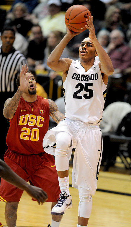 . Spencer Dinwiddie of CU puts up a shot on J.T. Terrell of USC during the second half of the January 10, 2013 game in Boulder.    Cliff Grassmick/Daily Camera
