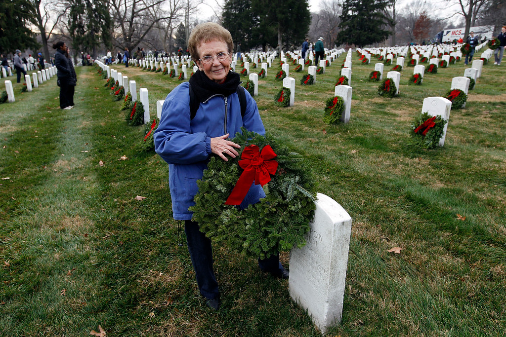 . Leona Zirnstein 80, of Emporia, Kan., places a wreath at a grave at Arlington National Cemetery in Arlington, Va., on Saturday Dec. 15, 2012, during Wreaths Across America Day. Wreaths Across America was started in 1992 at Arlington National Cemetery by Maine businessman Morrill Worcester and has expanded to hundreds of veterans\' cemeteries and other locations in all 50 states and beyond. (AP Photo/Jose Luis Magana)