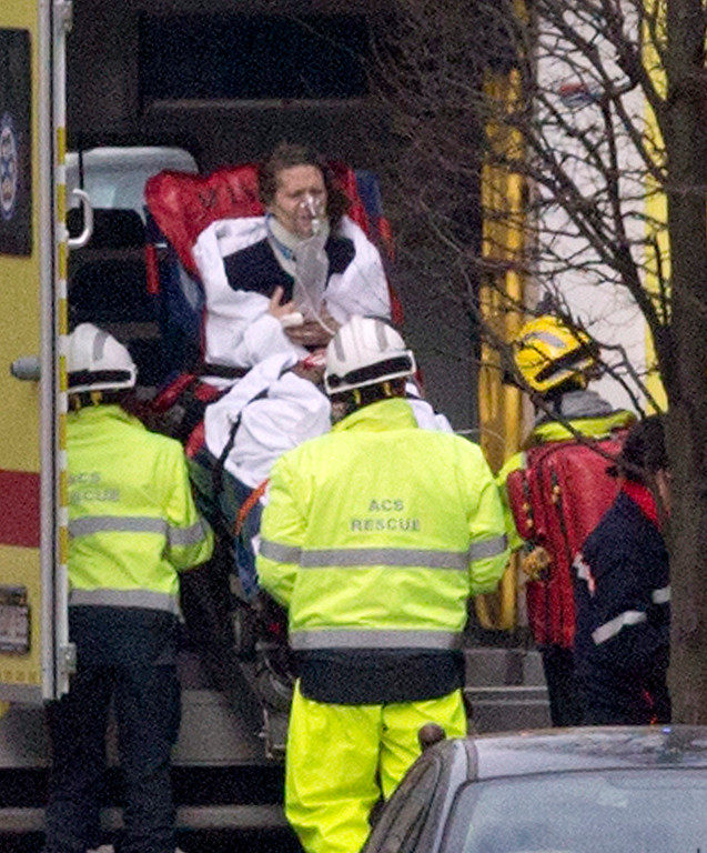 . A woman is evacuated in an ambulance by emergency services after a explosion in a main metro station in Brussels on Tuesday, March 22, 2016. Explosions rocked the Brussels airport and the subway system Tuesday, killing at least 13 people and injuring many others just days after the main suspect in the November Paris attacks was arrested in the city, police said. (AP Photo/Virginia Mayo)