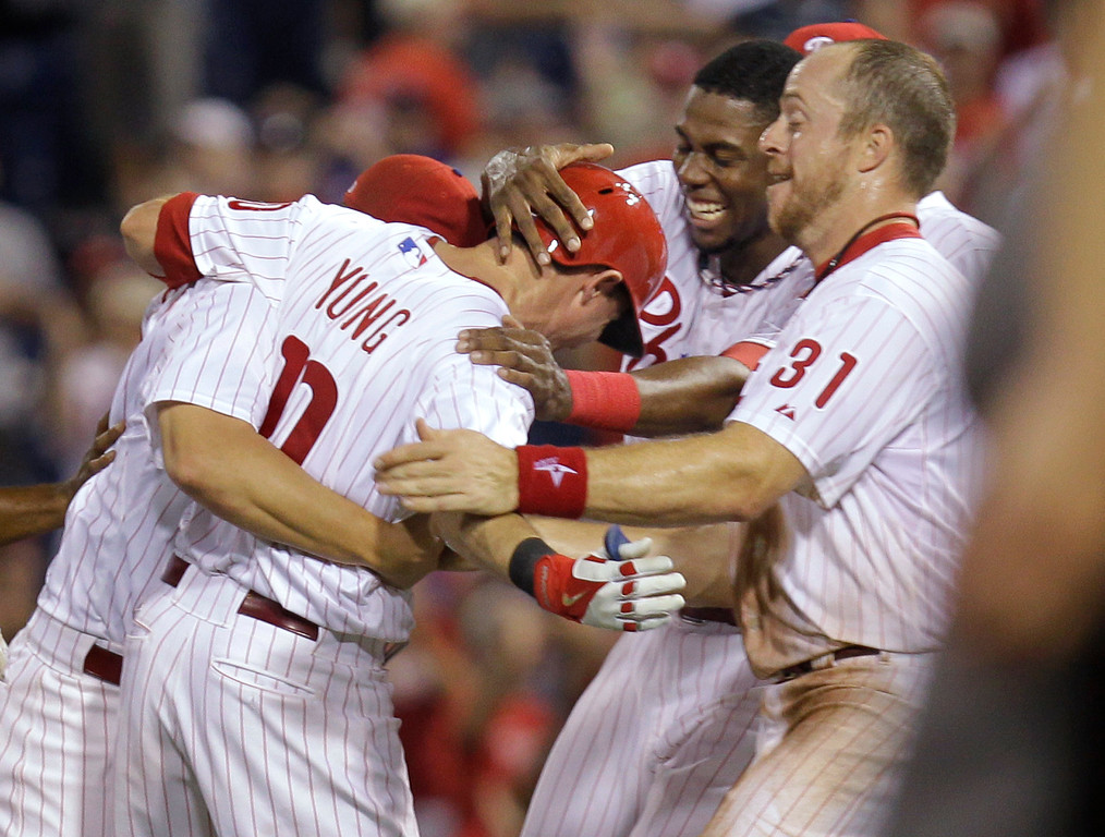 . \'Philadelphia Phillies\' Michael Young is rushed by John Mayberry Jr., second from right, and Erik Kratz (31) after his game-winning hit in the ninth inning against the Colorado Rockies in a baseball game, Wednesday, Aug. 21, 2013, in Philadelphia. The Phillies won 4-3. (AP Photo/Laurence Kesterson)