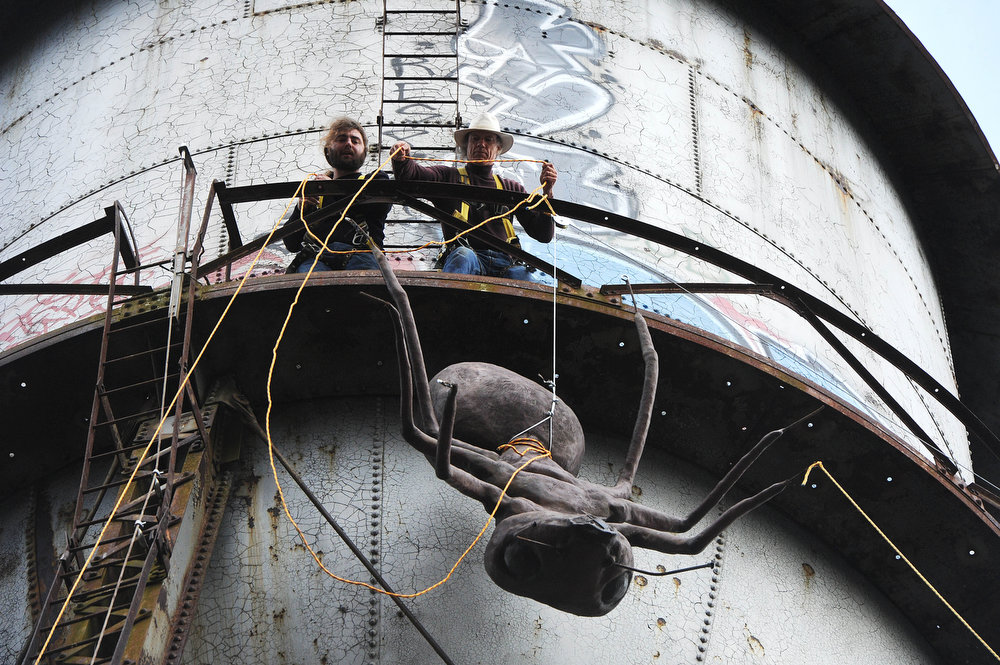 . Mark Cline and Lee Harris pull a large ant sculpture up to the top of a water tower at the abandoned Stillwater plant on Sunday, March 31, 2013, in Goshen, Va. Cline does an April Fools prank every year ó�this year, placing a large ant sculpture on top of the water tower in Goshen, Va. Cline is notorious in the Shenandoah Valley for his annual elaborate sculpture-based pranks, such as Foam Henge.  (AP Photo/The Daily News Leader, Katie Currid)