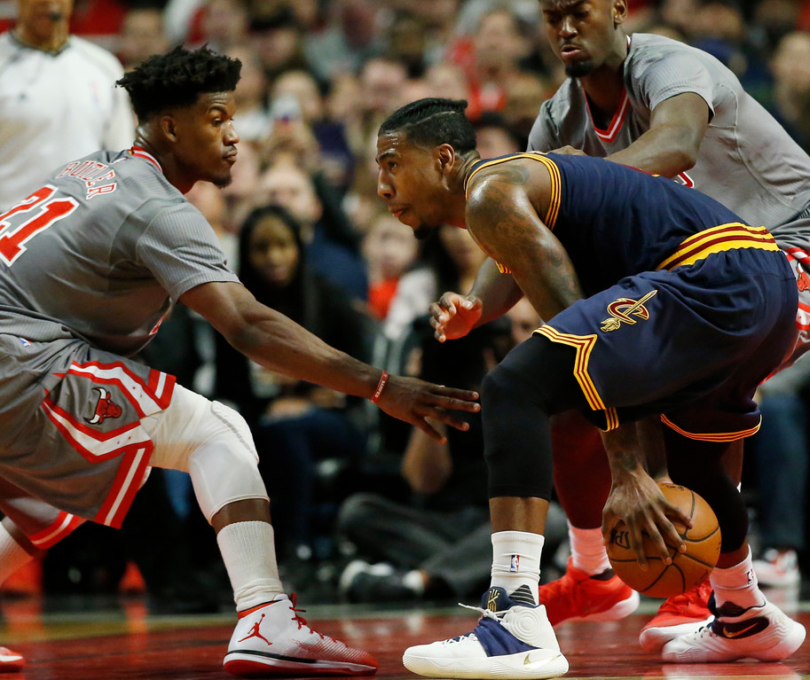 . Cleveland Cavaliers guard Iman Shumpert, right, controls the ball against Chicago Bulls guard/forward Jimmy Butler, left, and forward Bobby Portis during the second half of an NBA basketball game Thursday, March 30, 2017, in Chicago. (AP Photo/Nam Y. Huh)