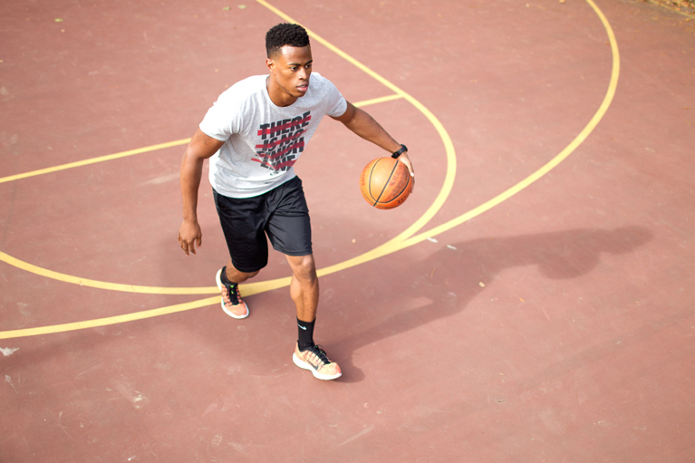 fitness model playing basketball on an outdoor court