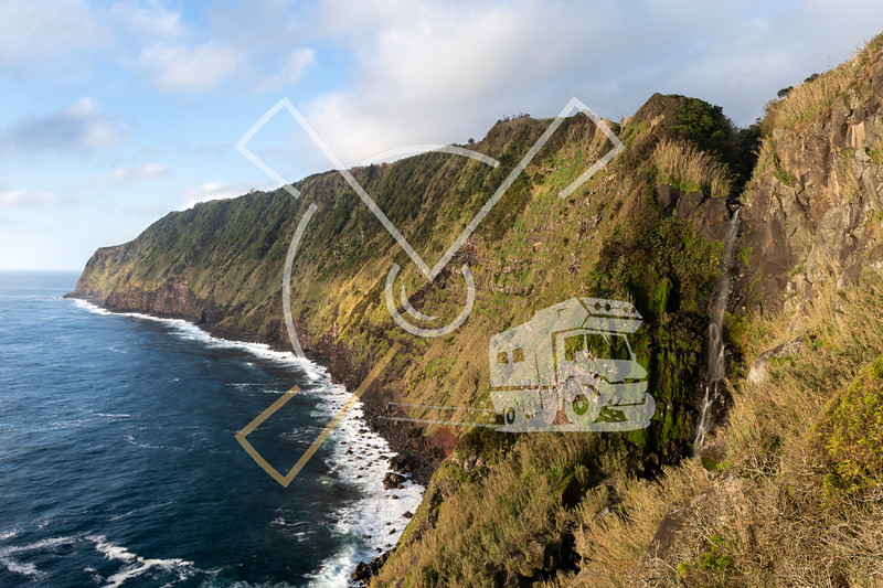 landscape image of Cascata da Ponta do Arnel waterfall showing the wild green cliffs of the eastcoast of São Miguel island on the Azores