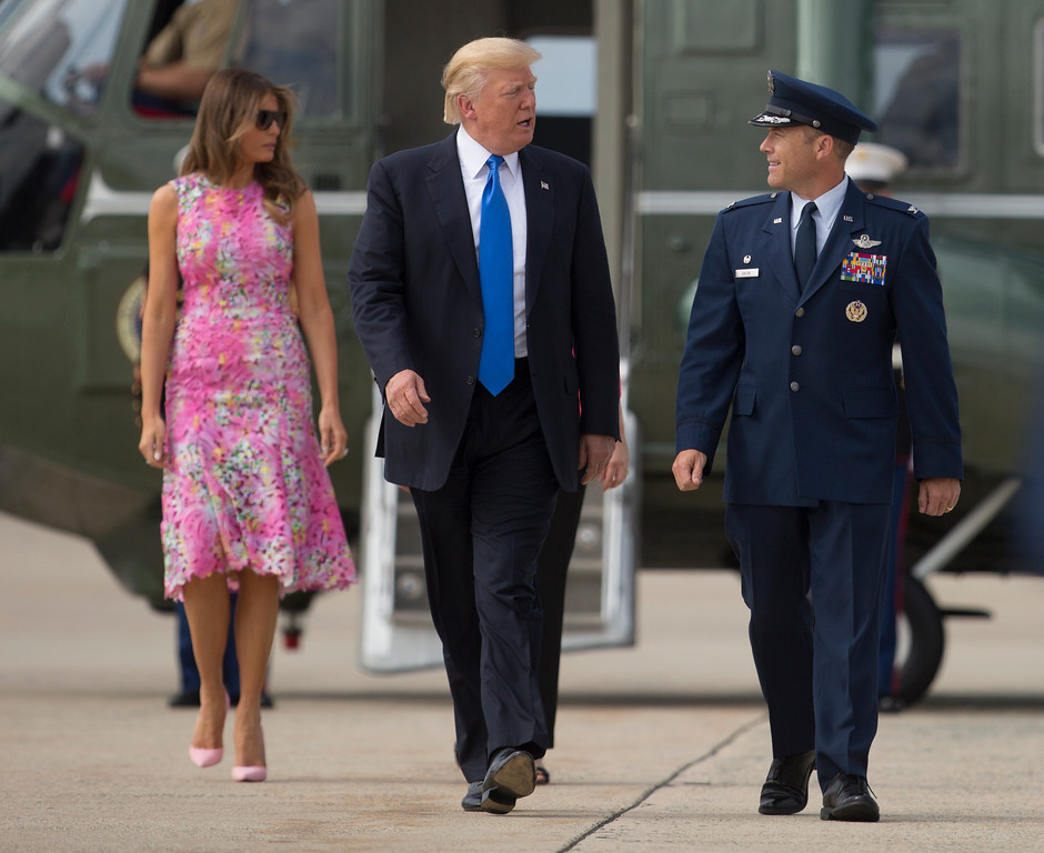 . President Donald Trump and first lady Melania Trump walk with U.S. Air Force Col. Casey Eaton, Commander, 89th Airlift Wing, from Marine One before boarding Air Force One, Tuesday, July 25, 2017, at Andrews Air Force Base, Md., en route to Youngstown-Warren Regional Airport in Vienna, Ohio. (AP Photo/Carolyn Kaster)