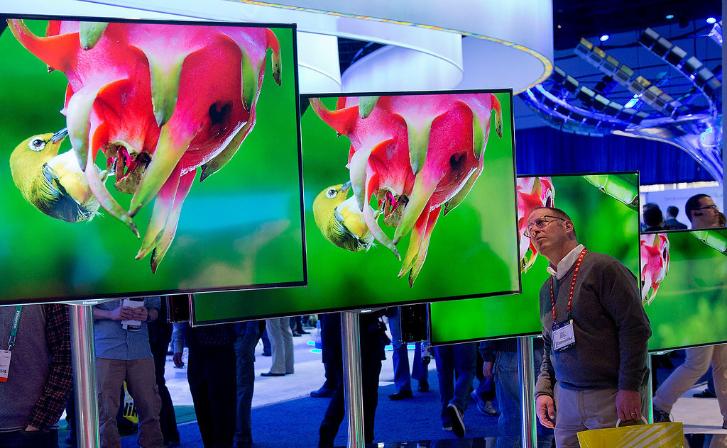 . Infastech engineer Dick Seidl examines a display of large screen LED Ultra HD televisions at the Hisense booth at the Consumer Electronics Show, Thursday, Jan. 10, 2013, in Las Vegas. (AP Photo/Julie Jacobson)