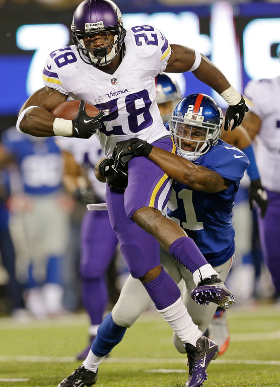 . Minnesota Vikings running back Adrian Peterson (28) is tackled by New York Giants\' Ryan Mundy (21) during the second half of an NFL football game Monday, Oct. 21, 2013 in East Rutherford, N.J. (AP Photo/Julio Cortez)