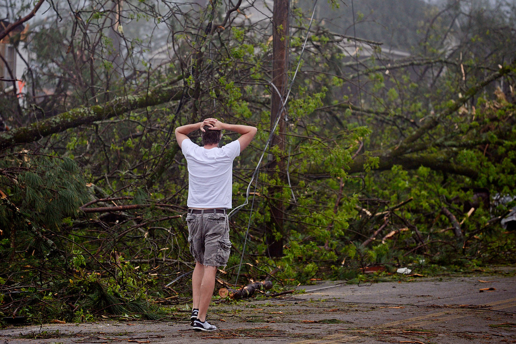 . Brent Martin walks along Kincannon Street in Tupelo, Miss., Tuesday, April 29, 2014. Martin was surveying damage done by a tornado to other homes in his neighborhood. (AP Photo/Thomas Graning)