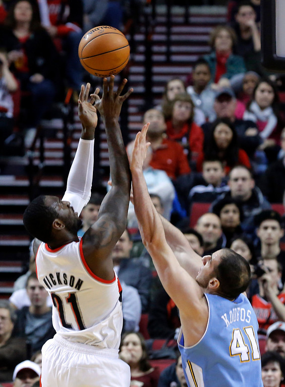 . Portland Trail Blazers center J.J. Hickson, left, shoots over Denver Nuggets center Kosta Koufos during the first quarter of an NBA basketball game in Portland, Ore., Thursday, Dec. 20, 2012. (AP Photo/Don Ryan)