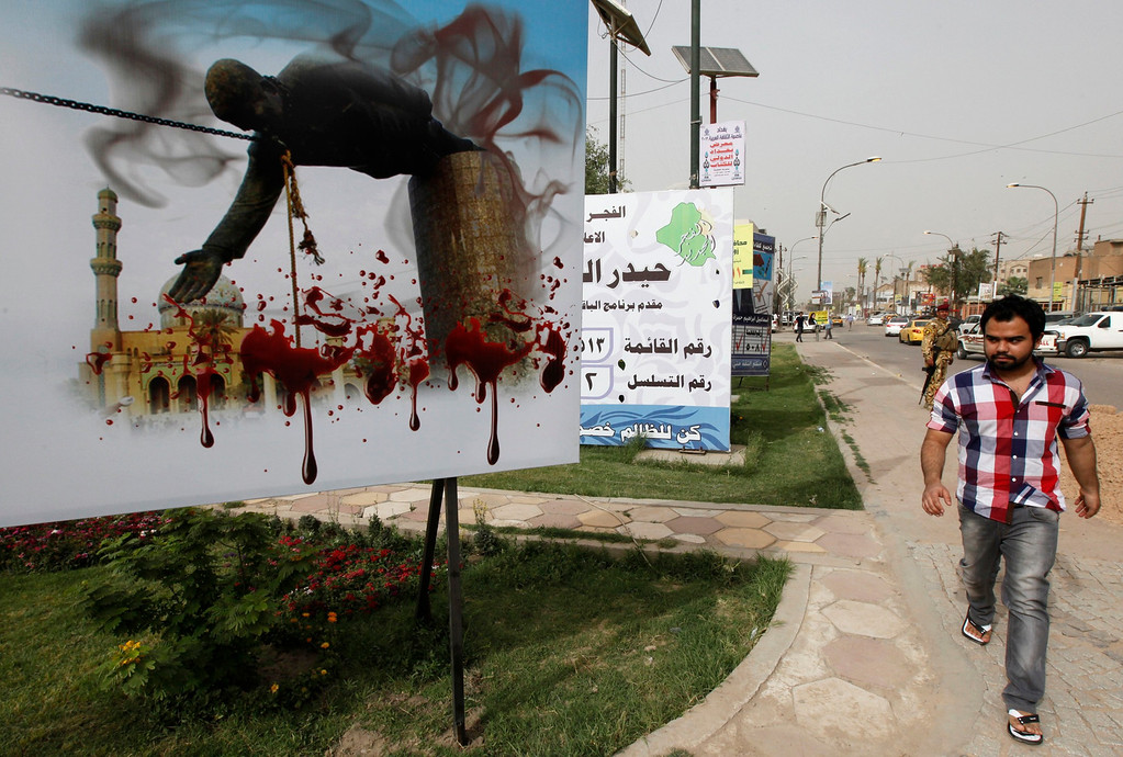 . An Iraqi man walks past a billboard depicting the fall of a statue of dictator Saddam Hussein in Baghdad April 9, 2013. A decade after the U.S.-led invasion, Iraq is still struggling with political instability and violence that in recent weeks has killed at least 10 candidates who had planned to run in forthcoming local elections.   REUTERS/Mohammed Ameen