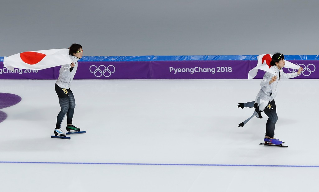 . Japan\'s Nao Kodaira, left, silver medal, and Miho Takagi, right, of Japan, bronze medal, skate with the national flag after the women\'s 1,000 meters speedskating race at the Gangneung Oval at the 2018 Winter Olympics in Gangneung, South Korea, Wednesday, Feb. 14, 2018. (AP Photo/Eugene Hoshiko)
