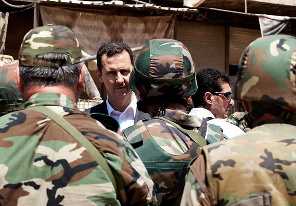 . This file image posted on the official Facebook page of the Syrian Presidency on Thursday, Aug. 1, 2013 purports to show Syrian President Bashar Assad talking with soldiers with during Syrian Arab Army day in Darya, Syria. More than two years into Syria\'s civil war, the once highly-centralized authoritarian state has effectively split into three distinct parts, each boasting its own flags, security agencies and judicial system. (AP Photo/Syrian Presidency via Facebook, File)