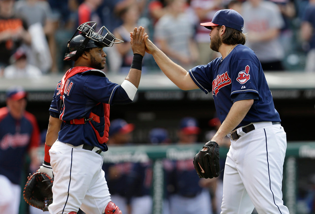 . Cleveland Indians catcher Carlos Santana, left, congratulates relief pitcher Chris Perez after the Indians defeated the Minnesota Twins 7-3. (AP Photo/Tony Dejak)