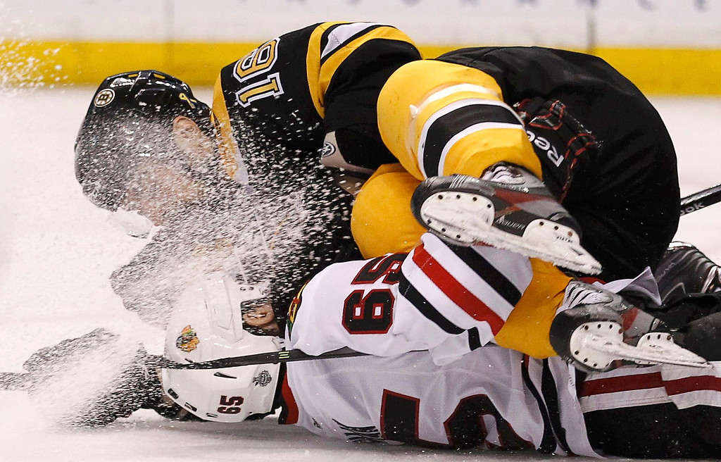 . Boston Bruins left wing Kaspars Daugavins fall on top of Chicago Blackhawks center Andrew Shaw during the third period in Game 4 of their NHL Stanley Cup Finals hockey series in Boston, Massachusetts, June 19, 2013.  REUTERS/Adam Hunger