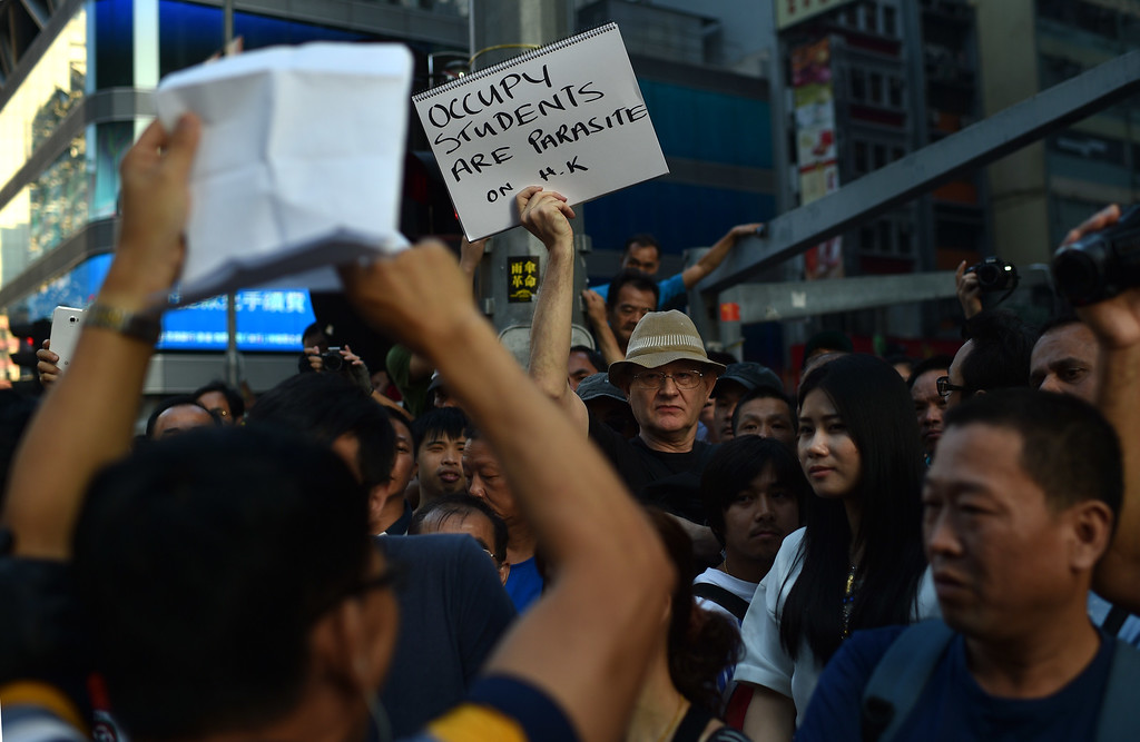 . A man holds a note protesting against pro-democracy demonstrators in front of a barricade in Mong Kok district in Hong Kong on October 18, 2014. Hong Kong\'s embattled government said it will open talks with student demonstrators Tuesday, after three nights of violent clashes between police and protesters who have paralysed parts of the city with mass pro-democracy rallies. AFP PHOTO/Pedro UgartePEDRO UGARTE/AFP/Getty Images