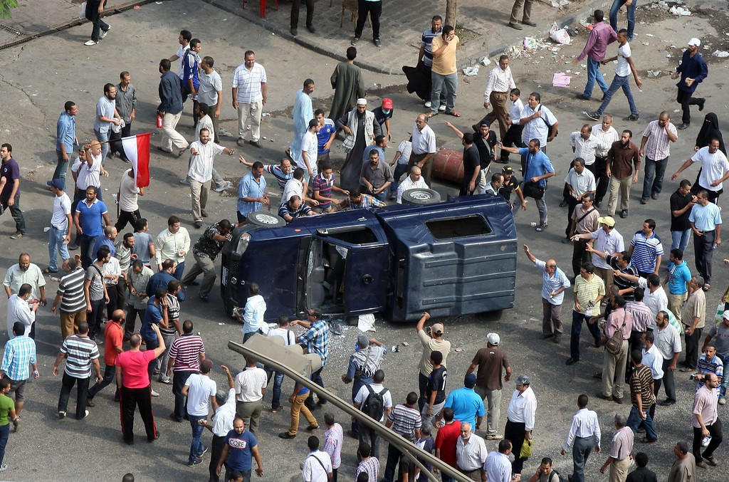 . Egyptian Muslim brotherhood supporter of Egypt\'s ousted president Mohamed Morsi overturn a police vehicle during clashes with riot police at Cairo\'s Mustafa Mahmoud Square after security forces dispersed supporters of Egypt\'s ousted president Mohamed Morsi on August 14, 2013.  AFP PHOTO / STR-/AFP/Getty Images