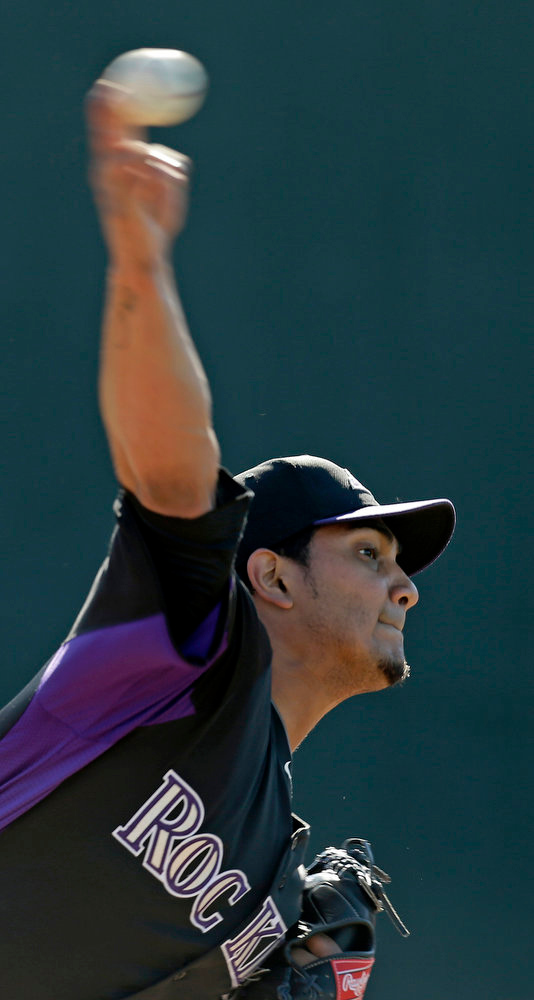 . Colorado Rockies\' Jorge De La Rosa throws during a spring training baseball workout Tuesday, Feb. 12, 2013, in Scottsdale, Ariz. (AP Photo/Darron Cummings)