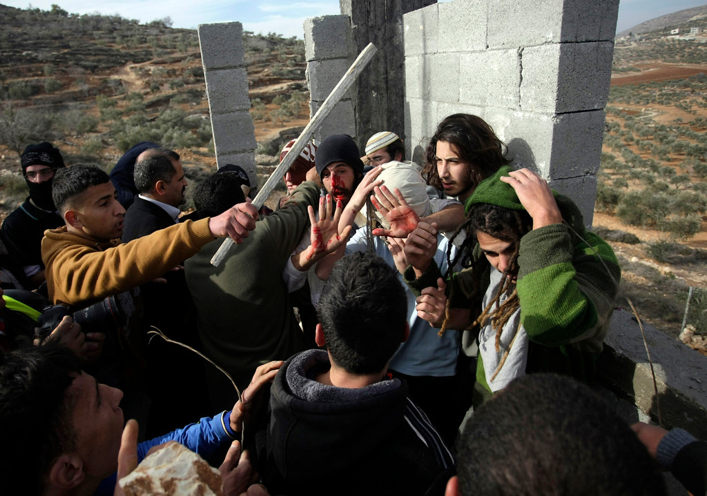 """. Palestinians hit Israeli settlers while others try to stop them before a group of settlers were detained by Palestinian villagers in a building under construction near the West Bank village of Qusra, southeast of the city of Nablus, Tuesday, Jan. 7, 2014. Palestinians held more than a dozen Israeli settlers for about two hours in retaliation for the latest in a string of settler attacks on villages in the area, witnesses said. The military said the chain of events apparently began after Israeli authorities removed an illegally built structure in Esh Kodesh, a rogue Israeli settlement in the area. In recent years, militant settlers have often responded to any attempts by the Israeli military to remove parts of dozens of rogue settlements, or outposts, by attacking Palestinians and their property. The tactic, begun in 2008, is known as \""""price tag.\"""" (AP Photo/Nasser Ishtayeh, File)"""