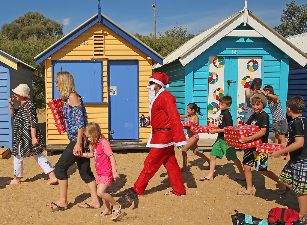 . MELBOURNE, AUSTRALIA - DECEMBER 25:  Santa Claus holds a beer as he walks with children holding their Christmas presents on Christmas Day at Brighton Beach on December 25, 2013 in Melbourne, Australia.  Brighton Beach features 82 colourful bathing boxes, which are one of the tourist icons of Melbourne. Temperatures in Melbourne on Christmas Day topped thirty degrees celcius.  (Photo by Scott Barbour/Getty Images)