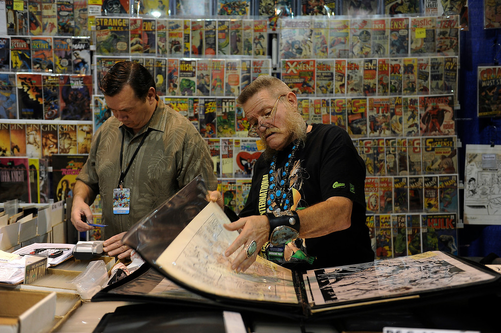 . DENVER, CO - JUNE 1: Rod Matlack of Pueblo, Colorado, right, thumbs through original pieces of comic book art at the Terry\'s Comics booth during Denver Comic Con at the Colorado Convention Center on June 1, 2013 in Denver, Colorado. (Photo by Seth McConnell/The Denver Post)