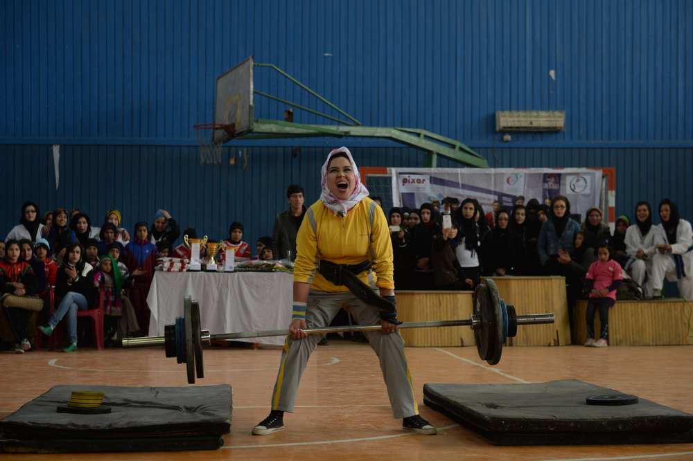Description of . An Afghanistan national powerlifting team member takes part in an event to mark International Women's Day in Kabul on March 8, 2014. In Kabul and major cities in Afghanistan, enormous progress has been made in women's rights since the 2001 US-led invasion brought down the Taliban regime that banned girls from going to school and women from working. But in remote areas where the traditional patriarchal system is very much the norm, life for most women has barely improved at all. (SHAH MARAI/AFP/Getty Images)