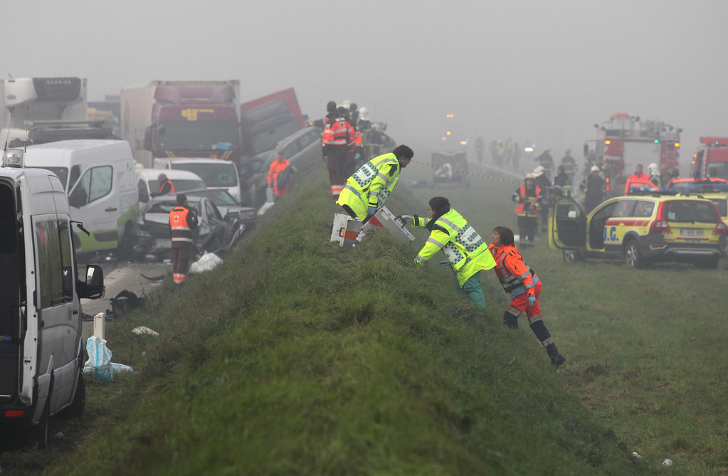 . Medics carry equipment to a crash scene on the A19 highway in Zonnebeke, western Belgium, Tuesday, Dec.3, 2013.   (AP Photo/Yves Logghe)