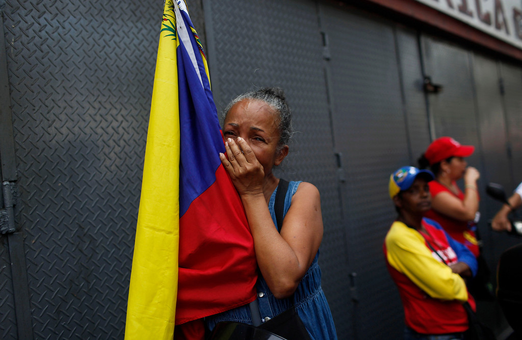 . A woman holding a Venezuelan flag cries as she watches the coffin containing the body of the late President Hugo Chavez be taken from the hospital, where he died on Tuesday, to a military academy in Caracas, Venezuela, Wednesday, March 6, 2013. (AP Photo/Rodrigo Abd)
