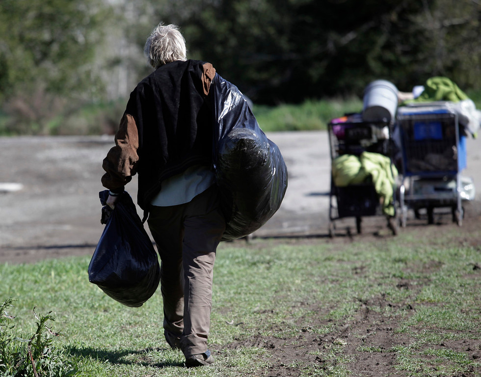 . Michael Stephens carries away his belongings as the city of San Jose leads a cleanup of a homeless encampment on Spring St. in San Jose, Calif. on Friday, March 8, 2013. The encampment has grown to over 100 people in the last six months. Most of the people relocated to this area after cleanup efforts took place in other parts of the city.  (Gary Reyes/ Staff)