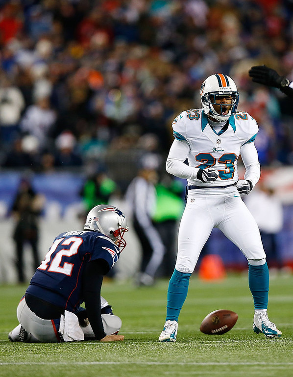 . Bryan McCann #23 of the Miami Dolphins celebrates a sack on Tom Brady #12 of the New England Patriots during the game at Gillette Stadium on December 30, 2012 in Foxboro, Massachusetts. (Photo by Jared Wickerham/Getty Images)