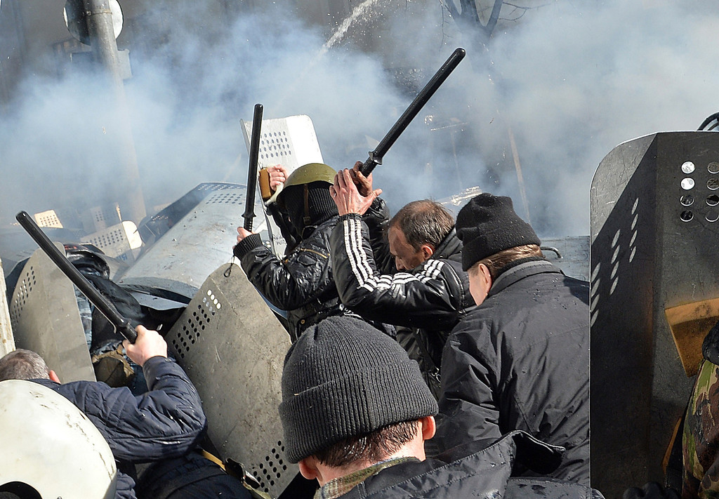 . Anti-government protesters clash with the riot police in the center of Kiev on February 18, 2014. Police on February 18 fired rubber bullets at stone-throwing protesters as they demonstrated close to Ukraine\'s parliament in Kiev, an AFP reporter at the scene said. Police also responded with smoke bombs after protesters hurled paving stones at them as they sought to get closer to the heavily-fortified parliament building.  AFP PHOTO / SERGEI  SUPINSKY/AFP/Getty Images