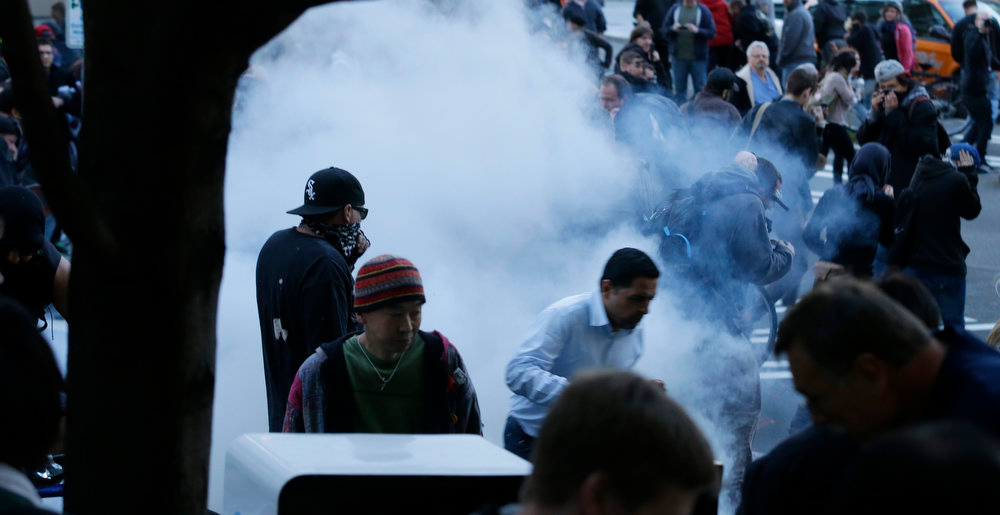 . Potesters react after police set up a flash-bang grenade and tear-gas bombs during a May Day march that began as an anti-capitalism protest and turned into demonstrators clashing with police lies on the ground next to police batons, Wednesday, May 1, 2013, in downtown Seattle. (AP Photo/Ted S. Warren)