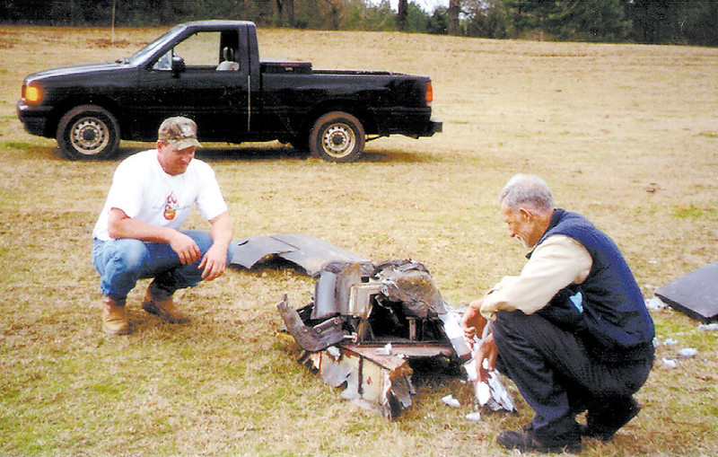 . Tracy Smith, left, and his father-in-law Don Crosby take a look at a large piece of debris believed to be from the space shuttle Columbia, Sunday, Feb. 2, 2003, near Alto, Texas. (AP Photo/The Lufkin Daily News, Marc R. Masferrer)