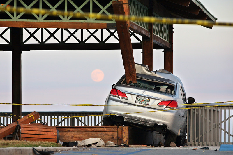 """101111 - BOCA RATON - City officials say a woman may have been trying to commit suicide when she drove her car """"at a high rate of speed,""""  through the parking area and straight into two wooden support columns. Those columns are now badly damaged. The car is pictured holding up the roof of the pavilion that is at the eastern end of Palmetto Park Road. Photo by Tim Stepien"""