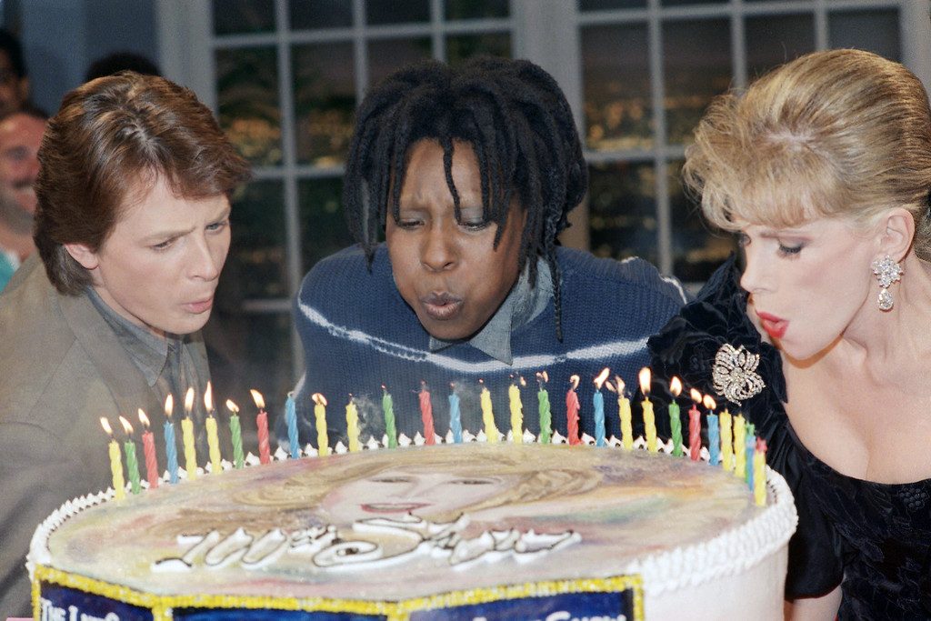 """. Late night talk show host Joan Rivers, right blows out candles on a special cake with the assistance of guests Whoopi Goldberg and Michael J. Fox following the taping of the 100th edition of \""""The Late Show Starring Joan Rivers\"""" at Fox Television Studios in Los Angeles on Wednesday, March 5, 1987. (AP Photo/Sunny Bak)"""