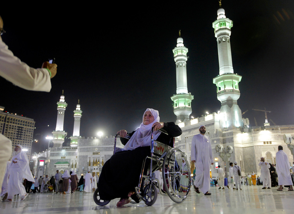 . An elderly Muslim pilgrim poses for a picture in front of the Grand Mosque in the holy city of Mecca, Saudi Arabia, late Tuesday, Oct. 8, 2013. The Muslim annual Hajj, or pilgrimage, that will begin on Oct. 14 this year, draws three million visitors each year, making it the largest yearly gathering of people in the world. (AP Photo/Amr Nabil)