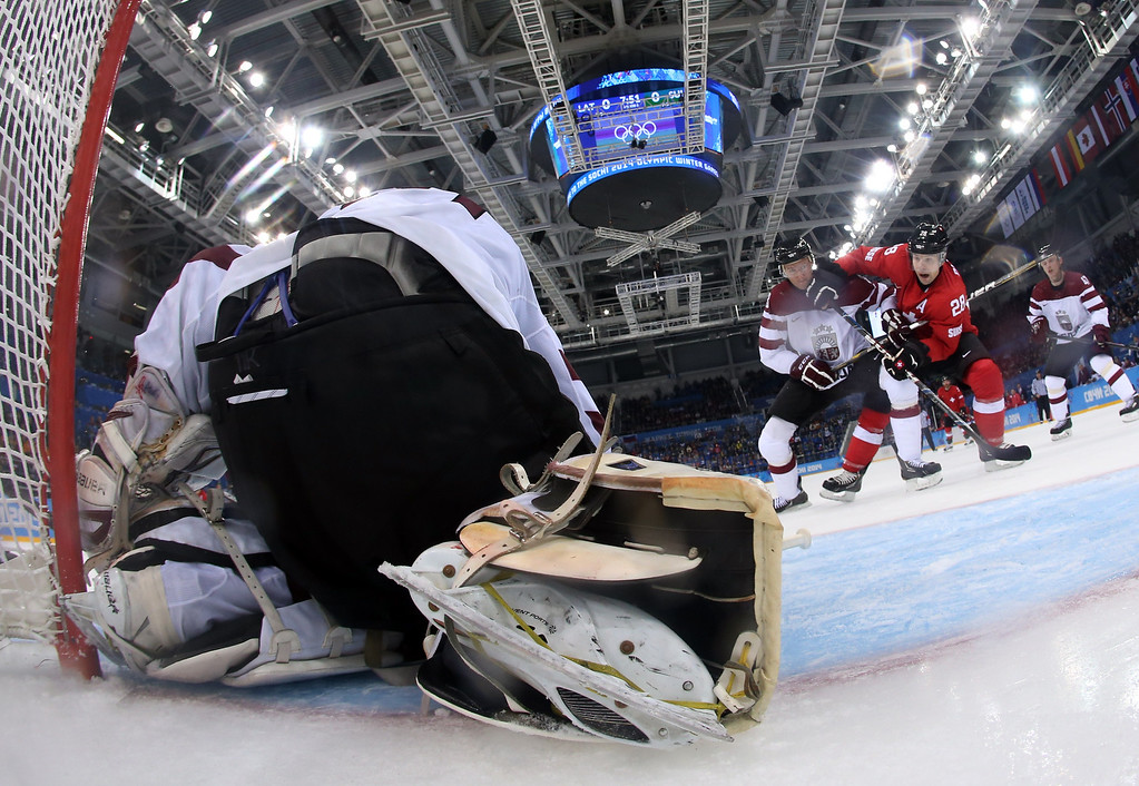 . Switzerland\'s Martin Pluss (R) vies for the puck with a Latvian player during the Men\'s Ice Hockey Group C match between Latvia and Switzerland at the Sochi Winter Olympics on February 12, 2014 at the Shayba Arena.    Martin Rose/AFP/Getty Images