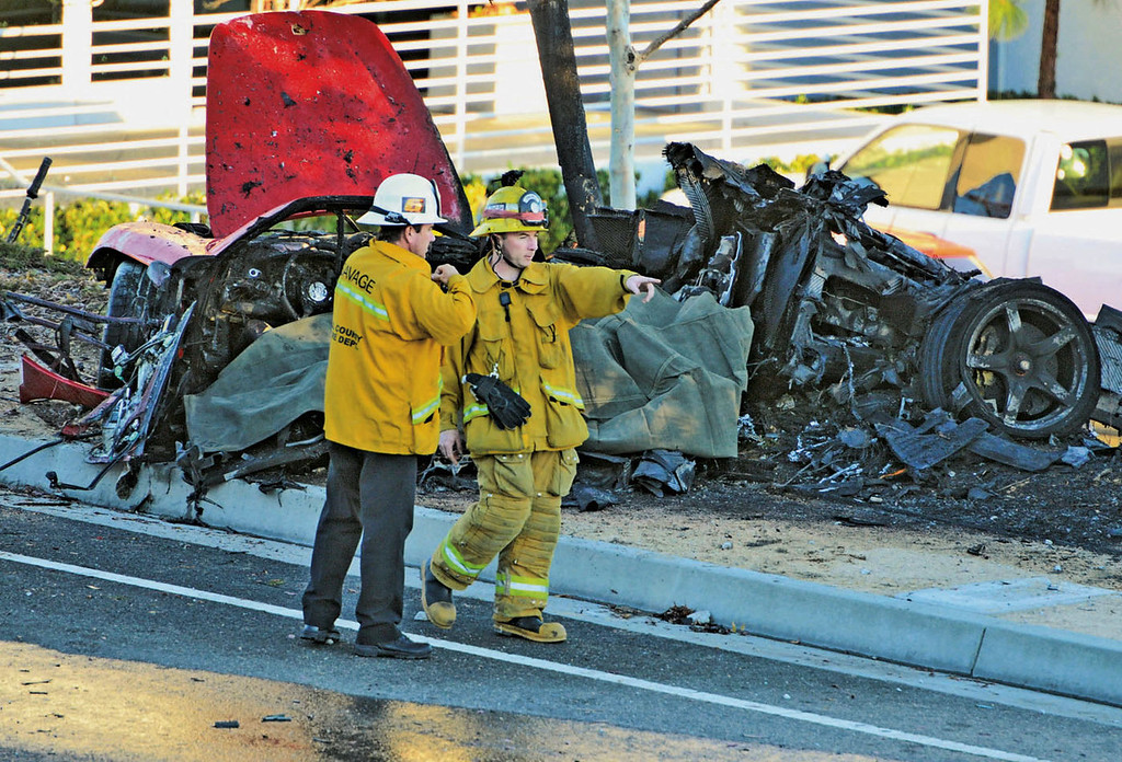 . First responders gather evidence near the wreckage of a Porsche sports car that crashed into a light pole on Hercules Street near Kelly Johnson Parkway in Valencia on Saturday, Nov. 30, 2013. (AP Photo/The Santa Clarita Valley Signal, Dan Watson)