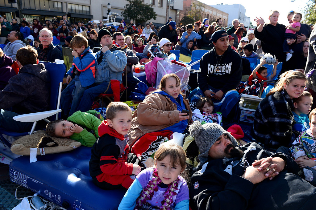 . David Bustamante, of Covina, lays down with his children as he watches the 125th Rose Parade in Pasadena, CA January 1, 2014. (Photo by Sarah Reingewirtz/Pasadena Star-News)