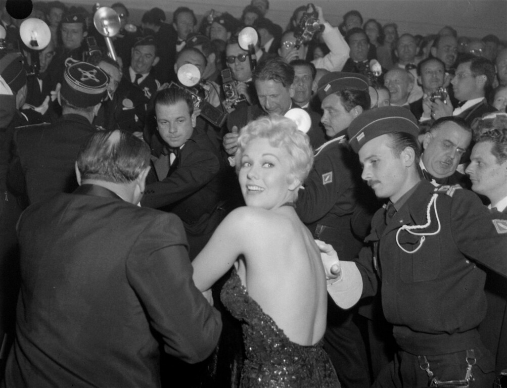 ". Illustrating why she was dubbed the ""Festival Bomb\"" at the Cannes Film Festival, actress Kim Novak is hustled through the crowd of media to attend an evening performance, April 25, 1956. (AP Photo)"