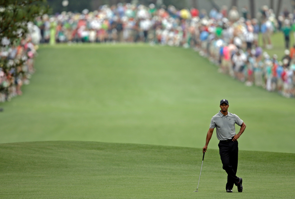 Description of . Tiger Woods waits to hit off the first fairway during the first round of the Masters golf tournament Thursday, April 11, 2013, in Augusta, Ga. (AP Photo/Matt Slocum)
