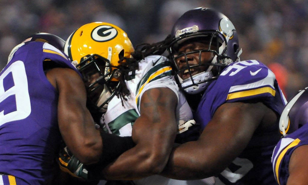 . Minnesota cornerback Xavier Rhodes, left, and defensive tackle Letroy Guion sandwich a Packer in the first quarter. (Pioneer Press: John Autey)
