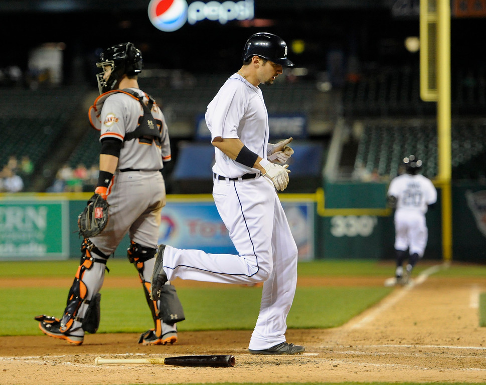 . Detroit Tigers\' Nick Castellanos scores past San Francisco Giants\' Buster Posey during the fifth inning of a baseball game Friday, Sept. 5, 2014, in Detroit. (AP Photo/Jose Juarez)