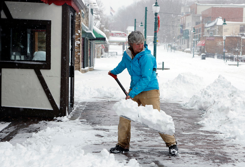 . Susan Bright shovels snow from the sidewalk in front of Nick\'s English Hut on Kirkwood, Wednesday, Dec. 26, 2012 in Bloomington, Ind. Bright said employees who couldn\'t walk to work were asked to stay home because roads are dangerous to drive on. (AP Photo/Bloomington Herald-Times, Jeremy Hogan)