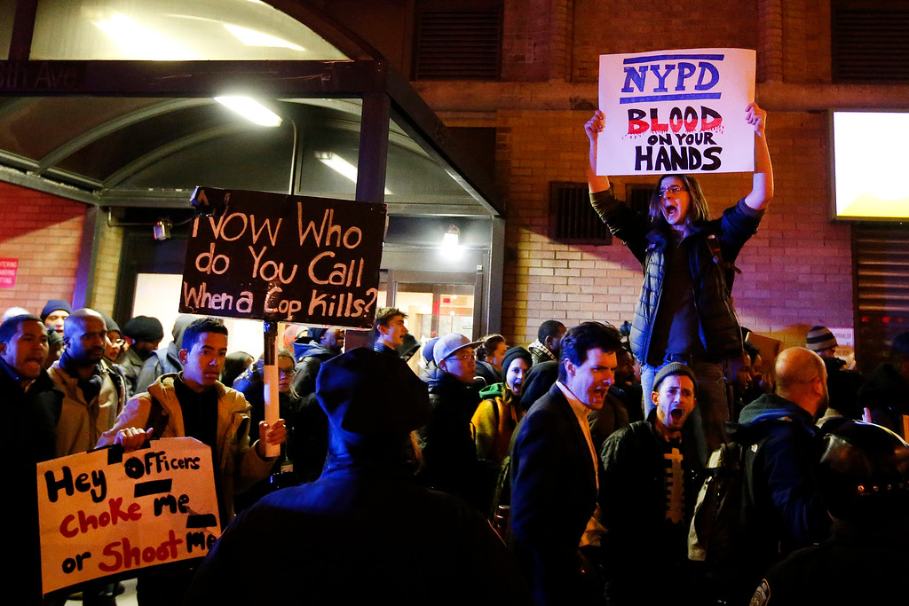 . Protesters rallying against a grand jury\'s decision not to indict the police officer involved in the death of Eric Garner chant as they pass police while marching through Midtown in the early morning hours of Friday, Dec. 5, 2014, in New York. (AP Photo/Jason DeCrow)